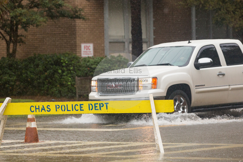 A pickup truck plows through floodwater past a police barrier along Calhoun Street in the historic district as Hurricane Joaquin brings heavy rain, flooding and strong winds as it passes offshore October 3, 2015 in Charleston, South Carolina.