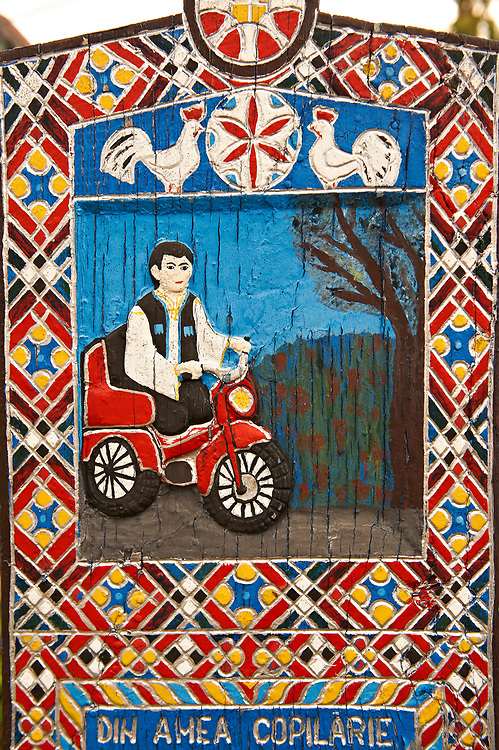 Tombstone of a disabled man,  The  Merry Cemetery ( Cimitirul Vesel ),  Săpânţa, Maramares, Northern Transylvania, Romania.  The naive folk art style of the tombstones created by woodcarver  Stan Ioan Pătraş (1909 - 1977) who created in his lifetime over 700 colourfully painted wooden tombstones with small relief portrait carvings of the deceased or with scenes depicting them at work or play or surprisingly showing the violent accident that killed them. Each tombstone has an inscription about the person, sometimes a light hearted  limerick in Romanian. .<br /> <br /> Visit our ROMANIA HISTORIC PLACXES PHOTO COLLECTIONS for more photos to download or buy as wall art prints https://funkystock.photoshelter.com/gallery-collection/Pictures-Images-of-Romania-Photos-of-Romanian-Historic-Landmark-Sites/C00001TITiQwAdS8