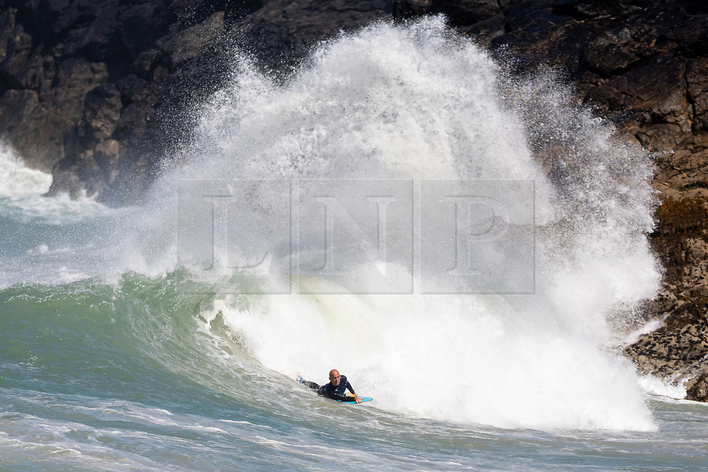 © Licensed to London News Pictures. 23/05/2020. Padstow, UK. A bodyboarder catches a wave near Padstow, Cornwall. There is currently no RNLI Lifeguard service in the county due to Coronavirus (Covid-19). The county has experienced unusual combination of large swell and warm weather during the bank holiday weekend. Photo credit : Tom Nicholson/LNP