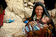 Maryam, 39, is holding her newborn granddaughter in front of the cave where her family dwell located inside the archaeological site of Bamiyan, central Afghanistan, an area mostly populated by Hazaras. The Buddhas of Bamiyan were two 6th century monumental statues of standing Buddhas carved into the side of a cliff in the Bamiyan valley in the Hazarajat region of central Afghanistan, situated 230 km northwest of Kabul at an altitude of 2500 meters. The statues represented the classic blended style of Gandhara art. The main bodies were hewn directly from the sandstone cliffs, but details were modelled in mud mixed with straw, coated with stucco. Amid widespread international condemnation, the smaller statues (55 and 39 meters respectively) were intentionally dynamited and destroyed in 2001 by the Taliban because they believed them to be un-Islamic idols. Once a stopping point along the Silk Road between China and the Middle East, researchers think Bamiyan was the site of monasteries housing as many as 5,000 monks during its peak as a Buddhist centre in the 6th and 7th centuries. It is now a UNESCO Heritage Site since 2003. Archaeologists from various countries across the world have been engaged in preservation, general maintenance around the site and renovation. Professor Tarzi, a notable An Afghan-born archaeologist from France, and a teacher in Strasbourg University, has been searching for a legendary 300m Sleeping Buddha statue in various sites between the original standing ones, as documented in the old account of a renowned Chinese scholar, Xuanzang, visiting the area in the 7th century. Professor Tarzi worked on projects to restore the other Bamiyan Buddhas in the late 1970s and has spent most of his career researching the existence of the missing giant Buddha in the valley.