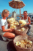 GREECE, CRETE Ayios Nikolaos, a fishing and tourism village; a fisherman selling sponges to a tourist in the harbor