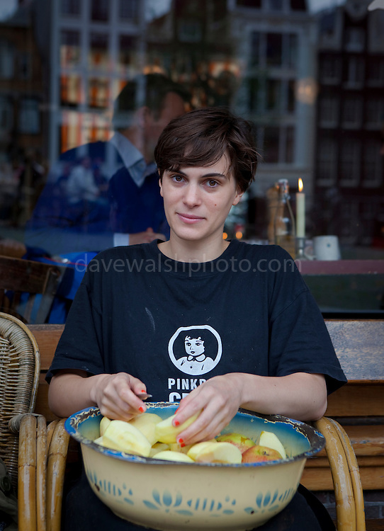 Young woman peeling apples outside the Villa Zeezicht Cafe, Amsterdam. Villa Zeezicht is considered to be one of the best places to get traditional Dutch apple pie in Amsterdam. And yes, it is good!