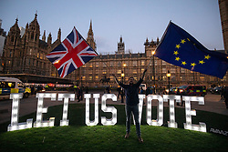 "March 27, 2019 - London, London, UK - London, UK. Campaigning group Avaaz install 1.2 metre-tall illuminated letters spelling out ""LET US VOTE"" outside the Houses of Parliament. This evening MPs are expected to vote on a series of indicative votes on alternative proposals to British Prime Minister Theresa May's withdrawal agreement. (Credit Image: © Tom Nicholson/London News Pictures via ZUMA Wire)"