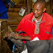 In his workshop, Robert Sang makes knives and saws and repairs shoes. He clearly enjoys his work, as we can see. He says he's looking forward to getting a youth group started here and to any opportunity it will give him to train other members of the village youth in developing their creativity. Village of Soba, located in Nandi County in Kenya's Rift Valley Province.