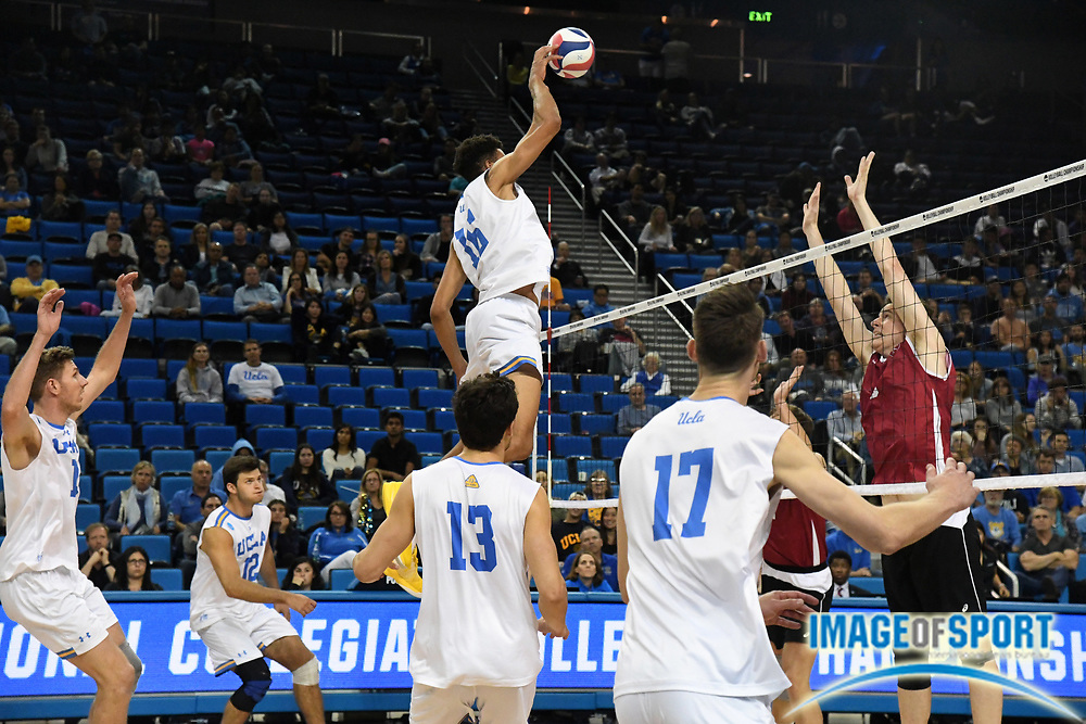 UCLA Bruins middle blocker Daenan Gyimah (16) spikes the ball against the Harvard Crimson during the opening round game of the NCAA college volleyball championship in Los Angeles, Tuesday, May 1, 2018. UCLA defeated Harvard 23-25, 25-21, 25-11, 25-21.