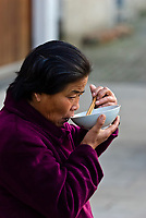 A woman eating noodles for breakfast along a canal in the water town of Zhouzhuang, China