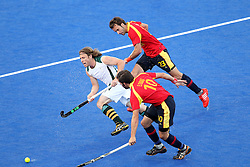 Jonathan Robinson of South Africa breaks through the defence of Eduard Tubau and David Alegre of Spain during Pool MA Hockey  match between South Africa and Spain held at the Riverbank Arena in Olympic Park in London as part of the London 2012 Olympics on the 3rd August 2012..Photo by Ron Gaunt/SPORTZPICS