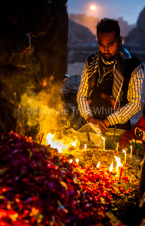 """8th January 2015, New Delhi, India. A man stands in quiet prayer by burning candles, incense sticks and flower petals left by believers hoping to get wishes granted by Djinns in the ruins of Feroz Shah Kotla in New Delhi, India on the 8th January 2015<br /> <br /> PHOTOGRAPH BY AND COPYRIGHT OF SIMON DE TREY-WHITE a photographer in delhi<br /> + 91 98103 99809. Email: simon@simondetreywhite.com<br /> <br /> People have been coming to Firoz Shah Kotla to leave written notes and offerings for Djinns in the hopes of getting wishes granted since the late 1970's. Jinn, jann or djinn are supernatural creatures in Islamic mythology as well as pre-Islamic Arabian mythology. They are mentioned frequently in the Quran  and other Islamic texts and inhabit an unseen world called Djinnestan. In Islamic theology jinn are said to be creatures with free will, made from smokeless fire by Allah as humans were made of clay, among other things. According to the Quran, jinn have free will, and Iblīs abused this freedom in front of Allah by refusing to bow to Adam when Allah ordered angels and jinn to do so. For disobeying Allah, Iblīs was expelled from Paradise and called """"Shayṭān"""" (Satan).They are usually invisible to humans, but humans do appear clearly to jinn, as they can possess them. Like humans, jinn will also be judged on the Day of Judgment and will be sent to Paradise or Hell according to their deeds. Feroz Shah Tughlaq (r. 1351–88), the Sultan of Delhi, established the fortified city of Ferozabad in 1354, as the new capital of the Delhi Sultanate, and included in it the site of the present Feroz Shah Kotla. Kotla literally means fortress or citadel."""