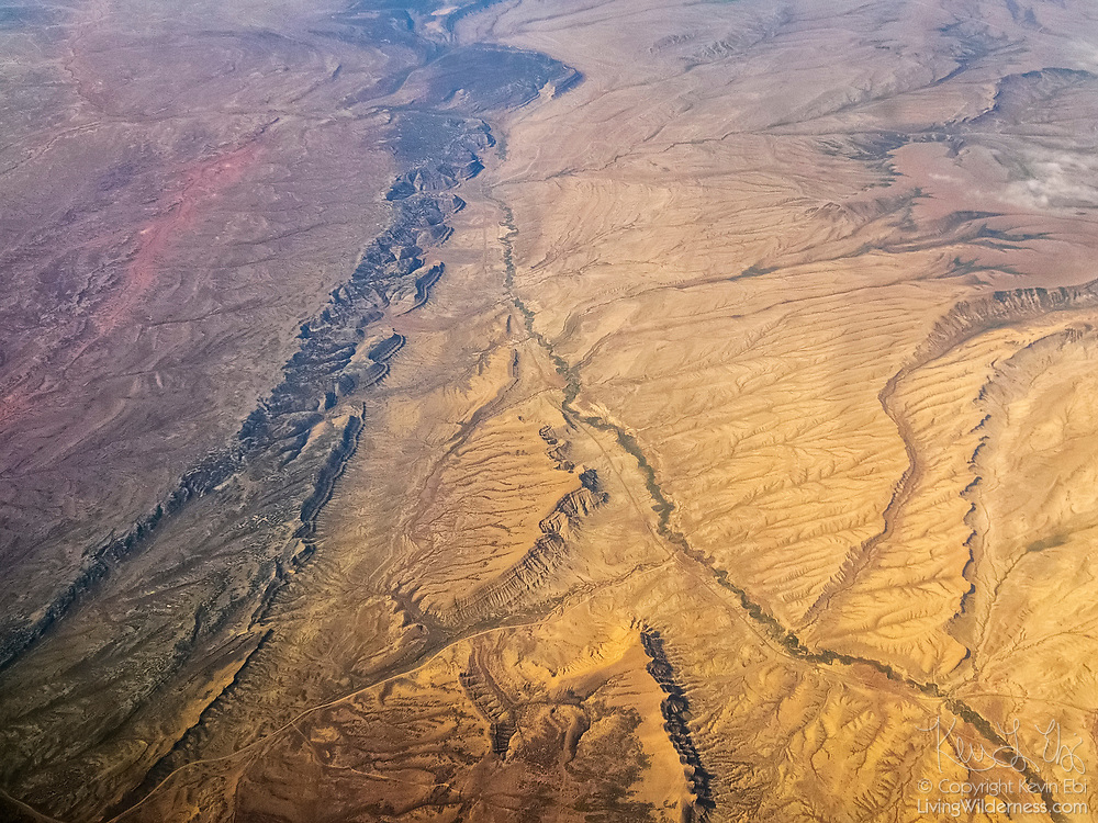The rugged, eroded texture of the Wyoming Basin landscape is visible in this aerial view captured near Sweeney Ranch, Wyoming.