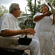 Maria de Jesus Hernandez laughs with Alberto Salinas as she shows him her recreation of musical instruments shaped like a bow and arrow. Matachines, a type of tribal dancers that believe in Niño Fidencio, would use the instrument in dances for the folk saint. <br /> Nathan Lambrecht/The Monitor