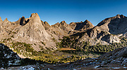 "In Cirque of the Towers, Pingora Peak rises above Lonesome Lake at sunrise, seen from Jackass Pass, in Bridger Wilderness, Wind River Range, Bridger-Teton National Forest, Rocky Mountains, Wyoming, USA. We backpacked to Big Sandy Lake Campground (11 miles round trip with 1000 feet gain). Two hours before sunrise, I departed from Big Sandy Lake to reach Jackass Pass viewpoint for Cirque of the Towers and Lonesome Lake (6.5 miles round trip, 1860 ft gain) on the Continental Divide Trail. The Continental Divide follows the crest of the ""Winds"". Mostly composed of granite batholiths formed deep within the earth over 1 billion years ago, the Wind River Range is one of the oldest mountain ranges in North America. These granite monoliths were uplifted, exposed by erosion, then carved by glaciers 500,000 years ago to form cirques and U-shaped valleys. This image was stitched from multiple overlapping photos."