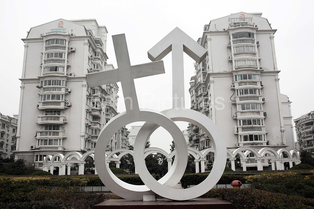 A statue featuring the intertwined male and female symbols stands in a housing complex in Shanghai, China on 14 December, 2009. Due to customs, owning an apartment or not plays a big role in determining the prospects of a young Chinese man finding a bride. Despite repeated efforts by government to rein in housing prices, housing in major cities in Shanghai and Beijing have changed little from their peaks  and the flow of hot money into smaller cities have fueled additional bubbles.