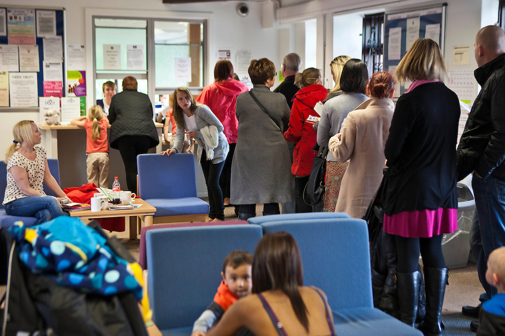 Families line up ready to book in for their visit. HMP Nottingham visitors centre run by the Prison Advice and Care Trust, PACT.