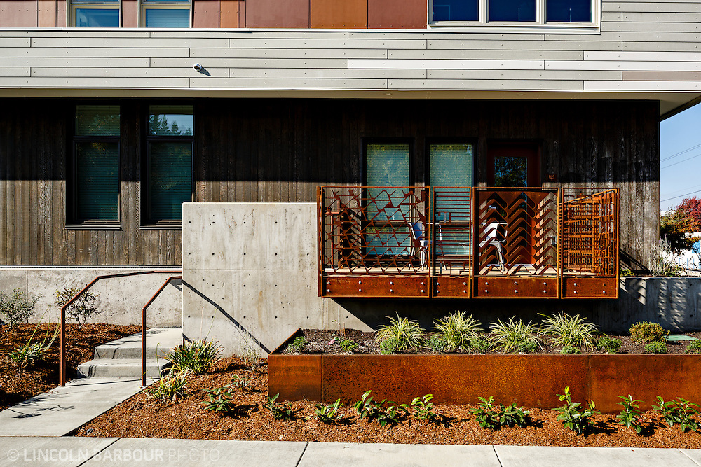 University House student housing apartment in Eugene, OR. Designed by Mahlum Architects. A view of a first level balcony with rusted iron railing and nicely manicured landscaping