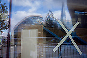 London's City Hall and the Shard is seen through a construction window with a taped cross.