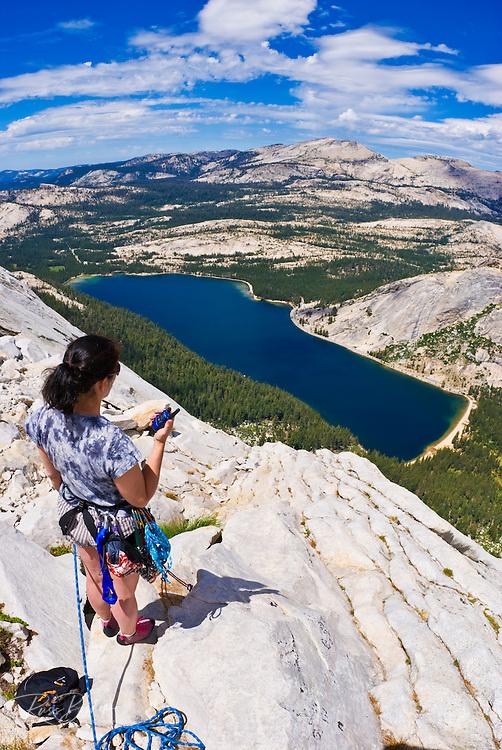 Climber using a radio on the Northwest Buttress of Tenaya Peak, Tuolumne Meadows area, Yosemite National Park, California