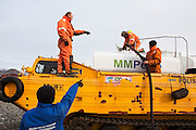 Grzegorz Karasinski (l-r), Robert Zmuda, Krysztof Herman, and Lukasz Gryglicki pump gasoline delivered by amphibious vehicle to storage tanks at the Polish Polar Station in Hornsund, Svalbard. The station operates year round and uses 90,000 liters of gasoline per year to operate generators, boats, snowmobiles, and heavy machinery.