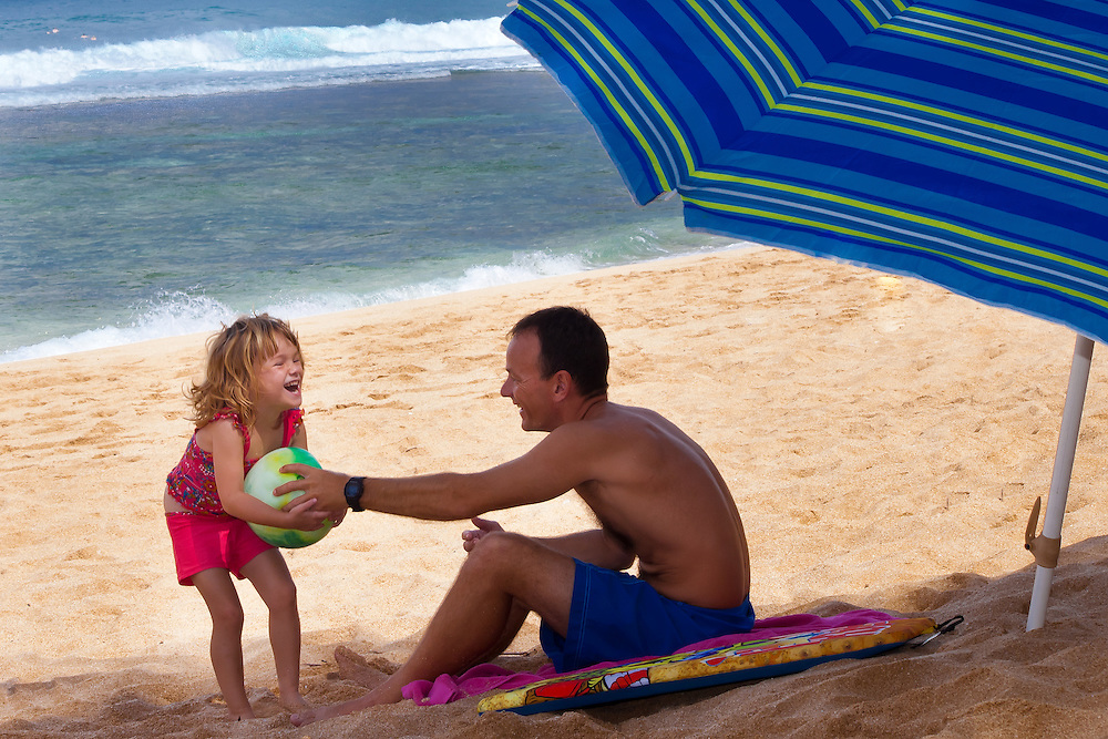 A little girl tugs on a ball her father is holding on the beach in Hawaii