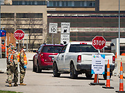 """26 APRIL 2020 - DES MOINES, IOWA: Soldiers with the Iowa Army National Guard watch people drive into the COVID-19 drive through testing site in Des Moines. Iowa started mass testing Saturday, with a drive through testing site in a parking lot in downtown Des Moines. The testing this weekend is considered a """"soft opening"""" for the program and tests were reserved for medical professionals and first responders. Despite numerous outbreaks in meat packing plants throughout Iowa, members of the public have not been able to get tested. On Saturday, 25 April, there were 5,092 confirmed cases of COVID-19 (Coronavirus / SARS-CoV-2) in Iowa (an increase of 647 since Friday, April 24) and 112 deaths in Iowa caused by COVID-19.         PHOTO BY JACK KURTZ"""
