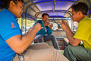 """13 MARCH 2013 - ALONG HIGHWAY 13, LAOS: Lao """"tuk-tuk"""" drivers play cards and wait for passengers about 100 meters from the Lao - Chinese border at the end of Highway 13 in the Boten Special Economic Zone. The SEZ is in Laos immediately south of the Lao Chinese border. It has turned into a Chinese enclave but many of the businesses struggle because their goods are too expensive for local Lao to purchase. Some of the hotels and casinos in the area have been forced to close by the Chinese government after reports of rigged games. The paving of Highway 13 from Vientiane to near the Chinese border has changed the way of life in rural Laos. Villagers near Luang Prabang used to have to take unreliable boats that took three hours round trip to get from the homes to the tourist center of Luang Prabang, now they take a 40 minute round trip bus ride. North of Luang Prabang, paving the highway has been an opportunity for China to use Laos as a transshipping point. Chinese merchandise now goes through Laos to Thailand where it's put on Thai trains and taken to the deep water port east of Bangkok. The Chinese have also expanded their economic empire into Laos. Chinese hotels and businesses are common in northern Laos and in some cities, like Oudomxay, are now up to 40% percent. As the roads are paved, more people move away from their traditional homes in the mountains of Laos and crowd the side of the road living off tourists' and truck drivers.    PHOTO BY JACK KURTZ"""