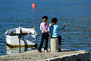 Two children (5 years old, 9 years old) throwing pebbles into water, moored small  boat in background. Korcula old town, island of Korcula, Croatia