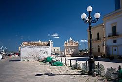 Vista laterale della piccolissima chiesetta di Santa Cristina, posta presso il Porto Peschereccio. La chiesa, costruita nel 1607, ha delle dimensioni davvero esigue e per lungo tempo è stata sconsacrata e adibita a deposito per le attrezzature da pesca. Piu in fondo è visibile la fontana greca, vero orgoglio della cittadina ionica e fresca di restauro.