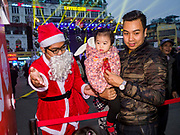23 DECEMBER 2017 - HANOI, VIETNAM: A Vietnamese man dressed Santa Claus directs a family to a free gift during a holiday street fair in the old quarter of Hanoi. The commercial and gift giving aspect of Christmas is widely celebrated in Vietnam and Vietnam's 5+ million Catholics celebrate the religious aspects of Christmas.     PHOTO BY JACK KURTZ