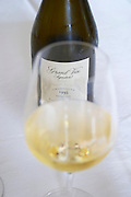 A wine glass filled with Jacquesson Grand Vin Signature Extra Brut Millesimee vintage 1995 on a white table cloth and a bottle in the background, Champagne Jacquesson in Dizy, Vallee de la Marne, Champagne, Marne, Ardennes, France