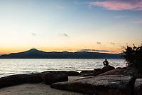 Silhueta de homem sentado sobre pedra na Praia da Daniela ao anoitecer. Florianópolis, Santa Catarina, Brasil. / Silhouette of a man sitting on a rock at Daniela Beach at dusk. Florianopolis, Santa Catarina, Brazil.