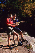 Couple stop to read a map while hiking.