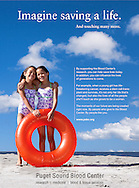 Puget Sound Blood Center ad of twin girls on beach with a large orange beach toy.