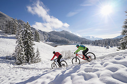 Mountain bikers moving down on snowcapped mountain