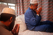 "A recuperating Muslim community Imam prays at the bedside of a patient who is staying on the Phyllis Friend surgical ward, Royal London Hospital, on 23rd June 1993, in Whitechapel, London England. The Royal London is one of London's oldest hospitals, having been founded in 1740 and is a major teaching hospital in Whitechapel, East London. It is part of the Barts and the London NHS Trust, alongside St Bartholomew's Hospital (""Barts""), which is a couple of miles away. Because of the cultural profile of East London, patients tend to be from many faiths, speaking many languages. (Photo by Richard Baker / In Pictures via Getty Images)"
