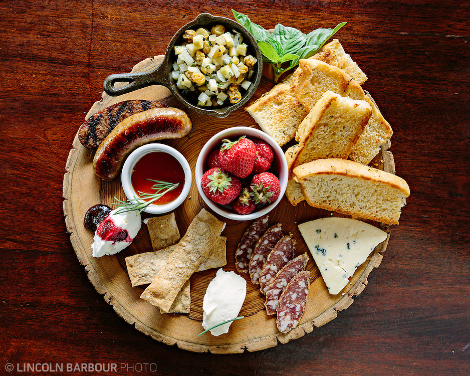 A rustic charcuterie display with sausage, cheese, salami, strawberries. Served on a tree round.