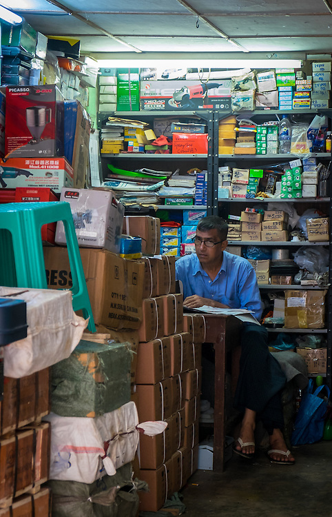 YANGON, MYANMAR - CIRCA DECEMBER 2013: Man looking at camera from a a hardware store in the streets of Yangon.