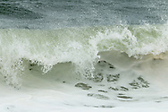White foam and spray as a wave breaks near shore at Cape Cod National Seashore.