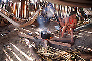 Margarita, a Yanomami who maintains a dedication to the traditions and heritage of her people in the face of increased Western influence, sits in her hut in a hammock, cooking yams over a wood fire. She is in the midst of a village in which many have assumed the traditions of Western visitors who ironically came to study the uninfluenced Yanomami peoples. Sejal, Venezuela. (Man Eating Bugs page 170,171)
