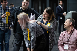 © Licensed to London News Pictures . 26/05/2019. Manchester, UK. A Liberal Democrat activist signs up to support Jo Swinson in the party's leadership campaign , using a fellow activist's back as a rest , as they watch results on TV screens in the counting hall . The count for seats in the constituency of North West England in the European Parliamentary election , at Manchester Central convention centre . Photo credit: Joel Goodman/LNP