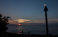 A torch burns as the people gather on Ka'anapali Beach to watch the sunset in Lahaina, Hawaii, on Sunday, Oct. 27, 2013. The island of Lanai is seen in the distance.  (© 2013 Cindi Christie/Cyanpixel)