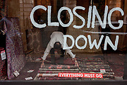 A man bends down to adjust a rug, in a shop window thats soon to close down and where everything must go, on 23rd September 2016, in Mayfair, central London, England.