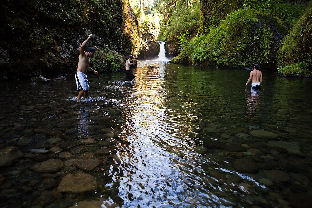 Young men wade into Eagle Creek below Punchbowl Falls, Columbia River Gorge National Scenic Area, Oregon.
