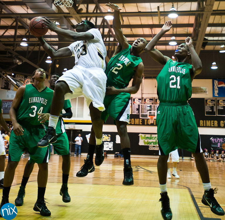 Concord's Xavier Stywall takes a shot against Kannapolis' Darius Rice and Chandler Reynolds Friday night at Concord High School. Concord won the game 77-51 to finish the season on top of the South Piedmont Conference. The SPC tournament starts next week. (Photo by James Nix)