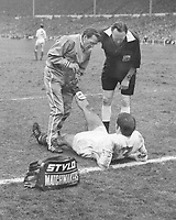 Football - 1970 FA Cup Final - Chelsea 2 Leeds United 2  11/04/1970<br />   <br /> Leeds trainer Les Cocker treats Terry Cooper for cramp with his Stylo matchmaker kit bag, as referee Eric Jennings looks on at Wembley.<br /> <br /> Credit Colorsport / Provincial Press