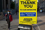 With the Coronavirus lockdown continuing into the Bank Holiday weekend, when Prime Minister Boris Johnson is due to tell the nation that only a gradual easing of regulations and social distancing rules are still to be in place, a person wearing a surgical mask walks towards a sign that supports emergency services workers such as the police has been attached to a crossing post in the City of London, the capitals financial district, on 7th May 2020, in London, England.