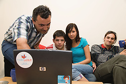 Group of friends in shared house looking at information on laptop,