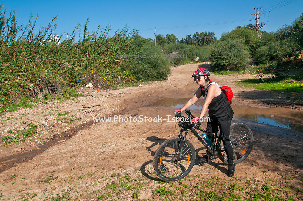 Outdoor winter cycling female cyclist cycling in nature on a clear sunny winter day