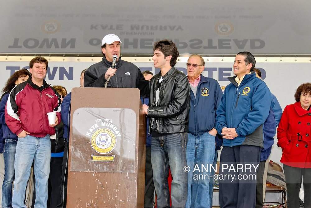 APRIL 16, 2011 - MERRICK, NY: Robbie Rosen, American Idol Season 10 contestant, at his hometown's Merrick Kid Fest on Robbie Rosen Day presented by Merrick Chamber of Commerce, with Nassau County Executive Edward P. Mangano speaking at podium, and Nassau Legislator Dave Denenberg of Merrick left of podium, and to right of podium: Assemblyman Dave McDonough of Merrick, Mark A. Bonilla Hempstead Town Clerk, and Legislator Norma Gonsalves in red coat, at Long Island, New York, USA. (EDITORIAL USE ONLY)