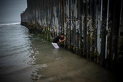 Olman Paz, from Progreso, Yoro, Honduras, looks through the wall that divides the US and Mexico at the Tijuana border.