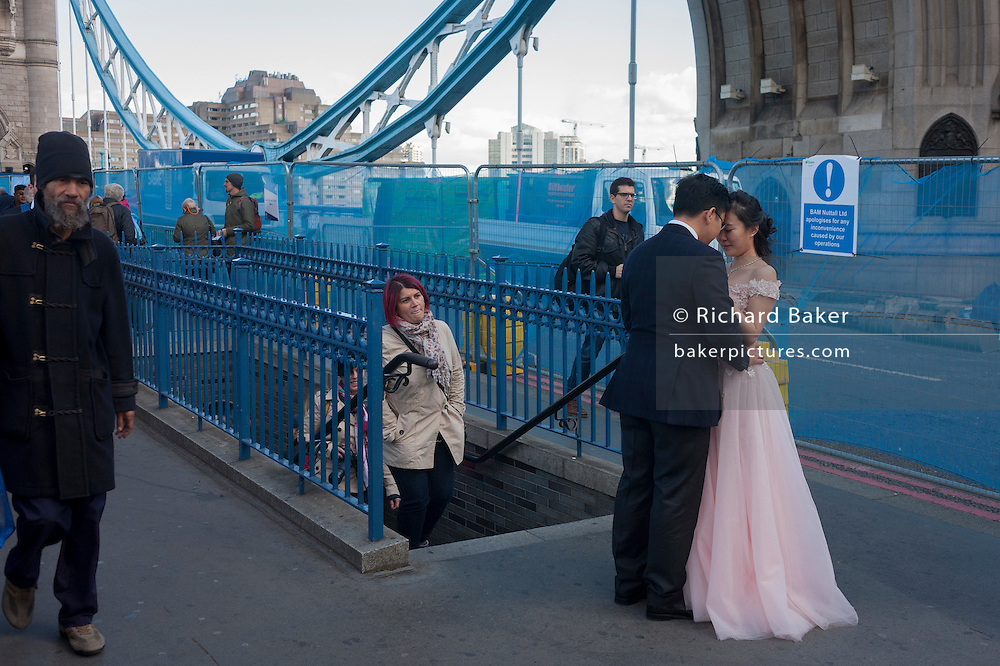 A Chinese couple have their weddng photos taken amid the chaotic repairs to London's Tower Bridge, closed to traffic and disrupting this major Thames crossing and surrounding roads for the next three months.
