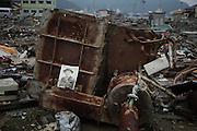 Photographie déposée au milieu des ruines, mémorial funeste ou acte despoir que cette personne ou ses proches repassent par là..La vague a tout dispersé. Aussi, lorsque des objets personnels sont retrouvés au milieu des décombres ils sont placés à la vue de tous à dessein de récupération.